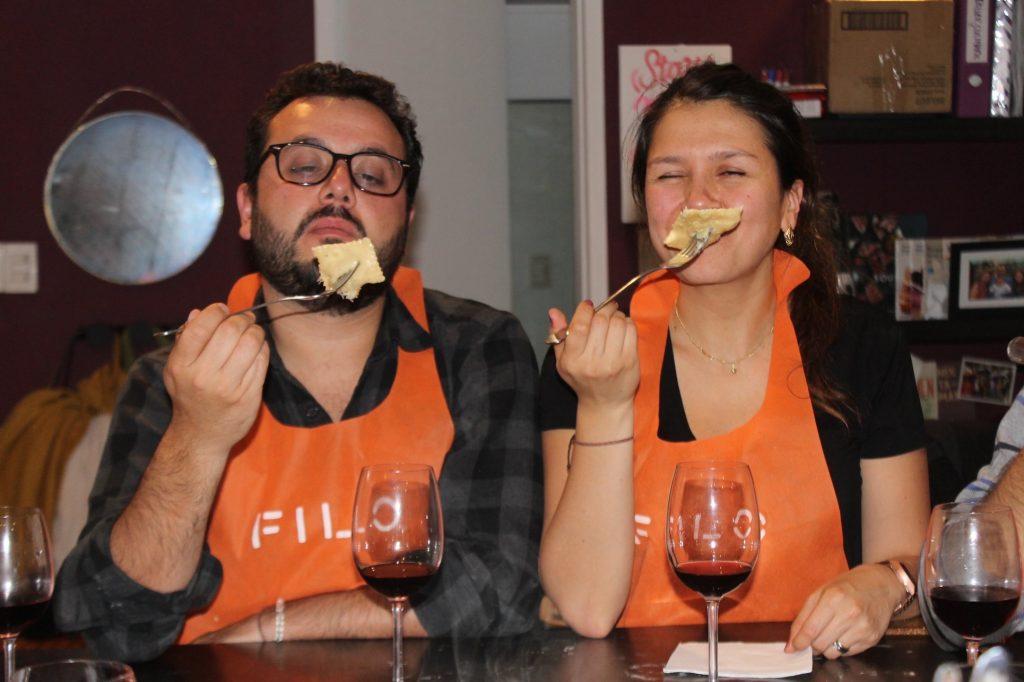 pareja comiendo pasta y vino en clase de cocina