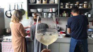 Anfitriones en cocina copa de vino blanco